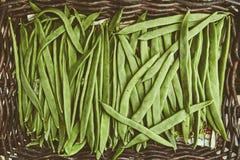 Organiska naturliga ofullbordade grönsaker med handikapp i en vide- korg på marknaden Naturliga ekologiska haricot vert, skidfruk Fotografering för Bildbyråer