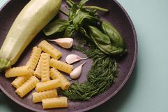 Organiska nya grönsaker kål, basilika, dill, pasta, vitlök i en stekpanna royaltyfri fotografi