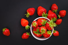 Organiska nya jordgubbar bär frukt i den vita koppen på svart Fotografering för Bildbyråer