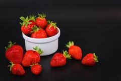 Organiska nya jordgubbar bär frukt i den vita koppen på svart Royaltyfri Fotografi
