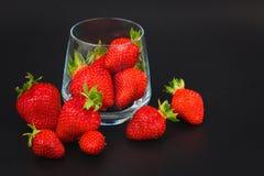 Organiska nya jordgubbar bär frukt i exponeringsglas på svart Royaltyfria Foton