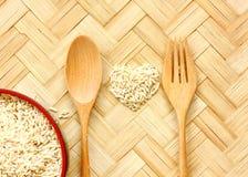 Organiska ris p? bambugolv rå ris i hjärtasmattrande royaltyfria foton
