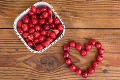 organiska självodlade körsbär på träbakgrund i hjärta formar Arkivbild