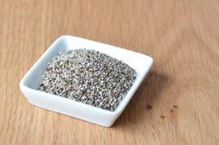 Organiska torra Chia Seeds i liten vit platta Arkivbilder