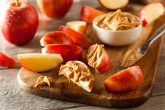Organiskt äpplen och jordnötsmör arkivbilder