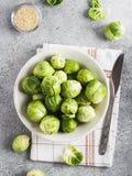 Organiskt för kål för Bryssel groddar nytt i krus på tabellen i kök Arkivbilder