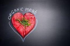 Organiskt kött för sunt äta Förbigår rått kött för hjärtaform med örter och text på svart svart tavlabakgrund arkivbild