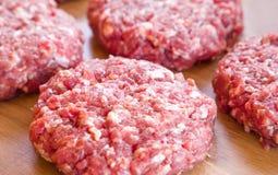 Organiskt rått jordnötkött, runda små pastejer för framställning av den hemlagade hamburgaren på träskärbräda Arkivbilder