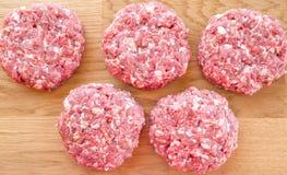 Organiskt rått jordnötkött, runda små pastejer för framställning av den hemlagade hamburgaren på träskärbräda Royaltyfria Foton