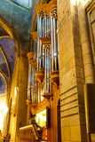 Organist playing on an old church organ. Seated on an elevated platform performing the music for the service royalty free stock images