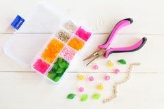 Organizador con las gotas, las flores plásticas y los accesorios para la joyería hecha a mano en el fondo de madera blanco Alicat Fotografía de archivo libre de regalías