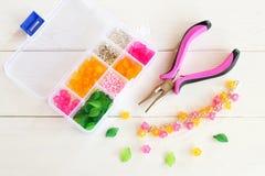 Organizador con las gotas, las flores plásticas y los accesorios para la joyería hecha a mano en el fondo de madera blanco Fotografía de archivo libre de regalías