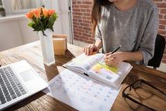 Organizador pessoal de Making Schedule On da mulher de negócios foto de stock