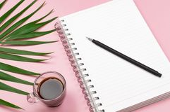 Working space: notepad, pen, cup of black coffee and green leaves. Flat-lay, top view. Pink background, minimalist composition. royalty free stock photos