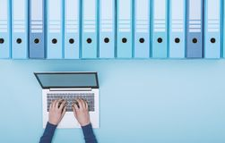 Searching files in the archive using a laptop. Organized archive with ring binders and woman searching for files in the database using a laptop, top view royalty free stock image