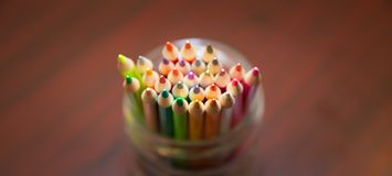Organized color pencil in a clear jar. Organized multi-color pencil in a clear jar sitting on a table royalty free stock images