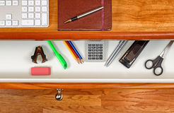 Organized desktop and open drawer with wooden floor underneath Royalty Free Stock Image