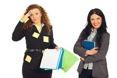 Organized and disorganized business women. Disorganized business women with folders and reminder notes on her suit and organized smiling business woman holding Stock Photos