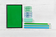 Organized supplies for work or school on desktop. Green spiral notepad with pencils, eraser, and paper clips on desktop. Pattern in colors of green and blue with Stock Images