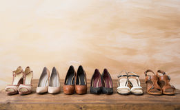 Organized woman`s shoes on wooden floor Royalty Free Stock Image