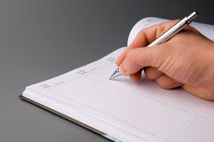 Organizer. Man holding pen and writing in weekly planner Stock Photos