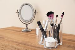 Organizer with cosmetic products for makeup and mirror on table. Against light wall royalty free stock photos