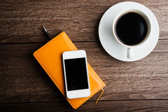 Organizer with cup of coffee and mobile phone Royalty Free Stock Images