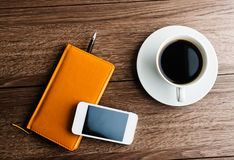 Organizer with cup of coffee and mobile phone Royalty Free Stock Photography