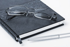 Organizer, glasses and pen. Business background Stock Images
