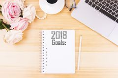 Organizer with 2018 goals list. Top view of organizer with 2018 goals placed on wooden female`s desktop. New Year`s resolution concept Royalty Free Stock Photo