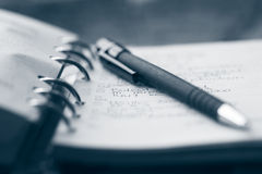 Organizer and pen. With shallow dof in blue duotone tint Stock Images