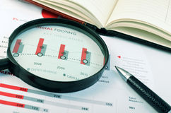 Organizer, pen, magnifying glass over graph Stock Images