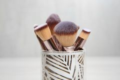 Organizer with professional makeup brushes against light background. Closeup royalty free stock photography