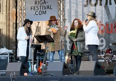 Organizers of 75th Anniversary of John Lennon festival in Riga. Smiling organizers with flowers on the scene of Tribute festival 75th Anniversary of John Lennon royalty free stock image