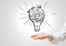 Organizing busineess process. A hand as if holding a picture of a bulb with stages of organizing a business process in it. White background. Concept of Royalty Free Stock Photo