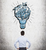 Organizing busineess process. A man with hands on hips standing in front of a picture of a bulb with stages of organizing a business process in it. Concrete Royalty Free Stock Photos