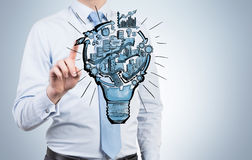 Organizing busineess process. A man touching a picture of a bulb with stages of organizing a business process in it. Greyish background. Front view. No face Stock Image