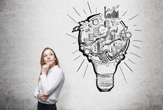 Organizing busineess process. Woman thinking about work, a picture of bulb with stages of organizing a business process in it. Concrete background. Concept of Stock Image