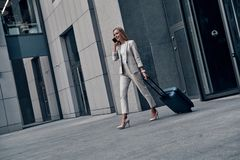 Organizing every minute. Full length of young woman in suit pulling luggage and smiling while walking outdoors stock photo