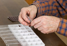 Organizing pills. Old man taking out pills from blister into pills box to organize weekly dose Royalty Free Stock Images