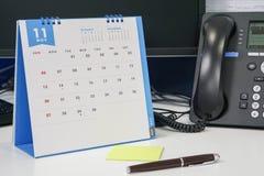 Organizzi la riunione di novembre sul calendario con la discussione del telefono Immagini Stock Libere da Diritti