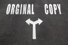 Orginal vs copy choice concept. Two direction arrows on asphalt Stock Image