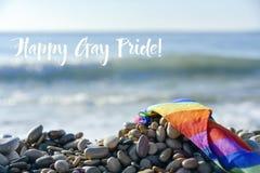 Orgullo gay feliz de la bandera y del texto del arco iris en la playa fotografía de archivo