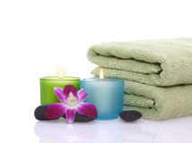 Orichid and candle before green towel Stock Photos