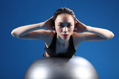 Oriental Asian woman back stretch on exercise ball. Back stretch during workout by a beautiful young oriental asian woman on fitness exercise ball. She is Royalty Free Stock Photography