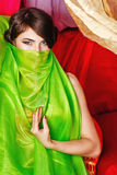Oriental beauty covers her face with a shawl stock photography