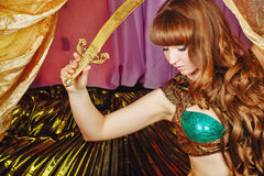 Oriental Beauty holding a sword. Sexy oriental beauty holds in her hands sword of Damascus steel. The concept of the Arab harem Stock Photography