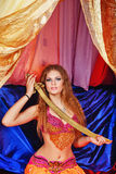 Oriental Beauty holding a sword. Sexy oriental beauty sitting in a tent and holding a sword with both hands. The concept of the Arab harem Stock Photo