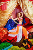 Oriental Beauty holding a sword. Sexy oriental beauty in a tent and sword in hand abuts her hip. The concept of the Arab harem Stock Photos