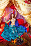 Oriental Beauty holding a sword. Oriental beauty sitting in a tent and holding a sword. The concept of the Arab harem Stock Image